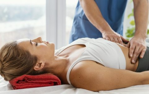 front-view-of-male-osteopathic-therapist-checking-female-patient-s-abdomen_23-2148846617