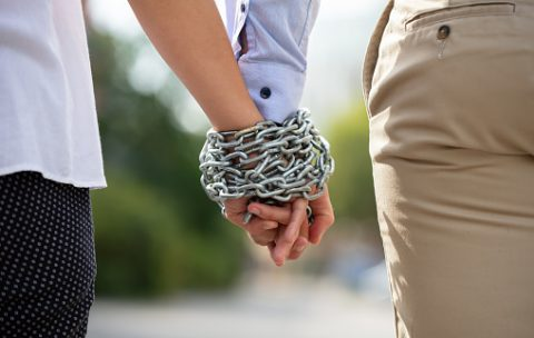 Rear View Of Couple's Hand Tied With Metal Chain At Outdoors
