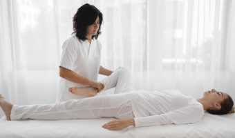 osteopathist-treating-a-young-woman-at-the-hospital_23-2148776243