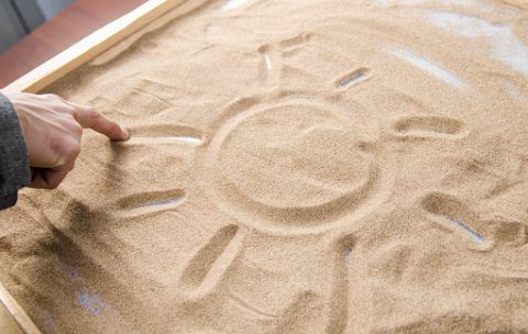 a man draws by his  finger on the sand symbol of the sun