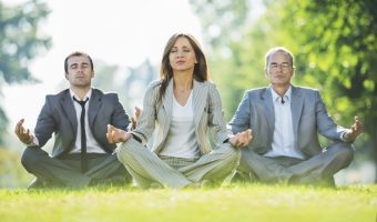 Business people exercising yoga in park.